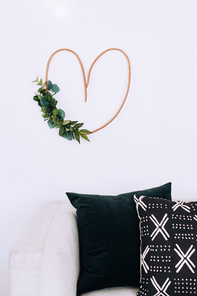 heart-shaped DIY minimalist wreath with Eucalyptus over couch with pillows