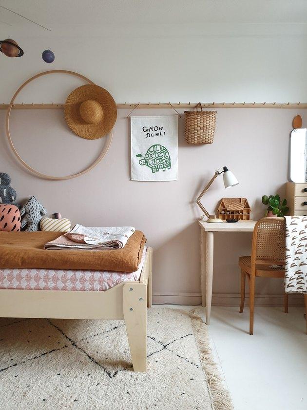 pink and brown minimalist girl bedroom with hula hoop and peg rail