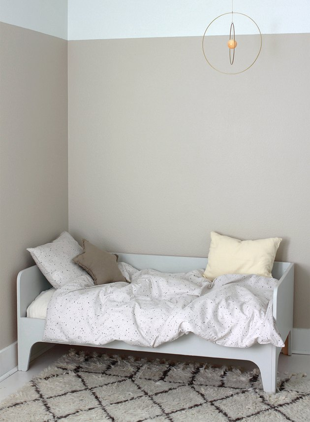 taupe minimalist girl bedroom with gold mobile and star pillow
