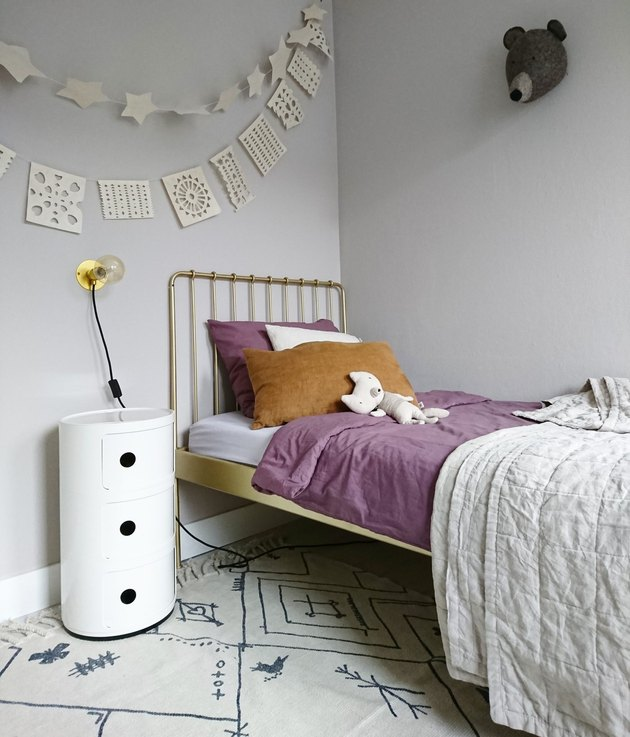 minimalist girl bedroom with brass bed