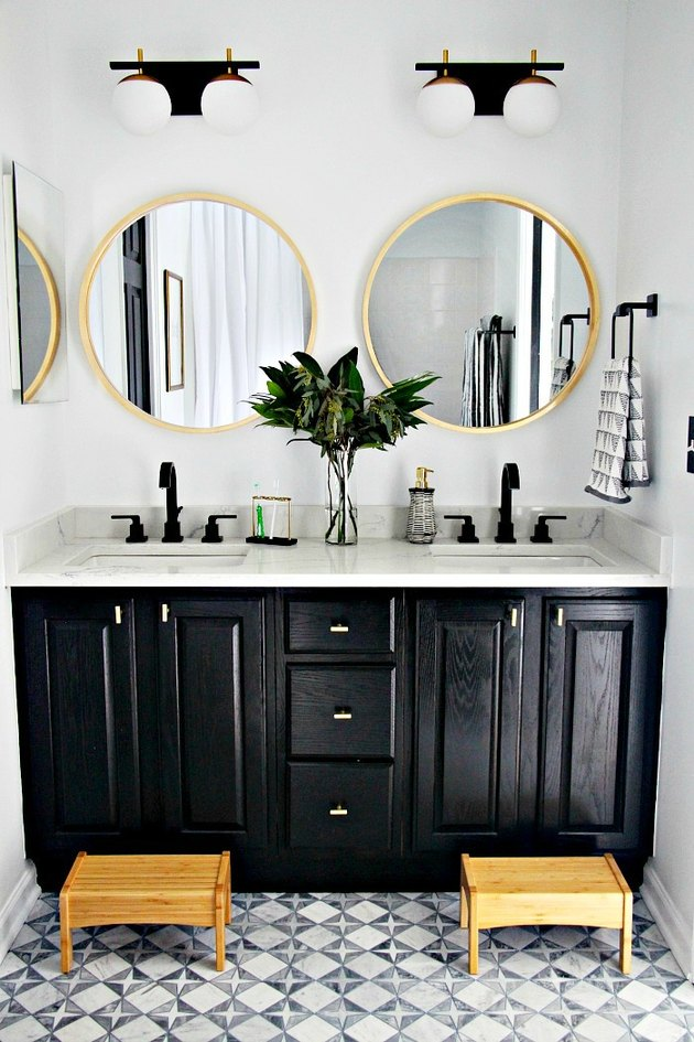 Star-shaped art deco tile floor with black cabinets in modern bathroom
