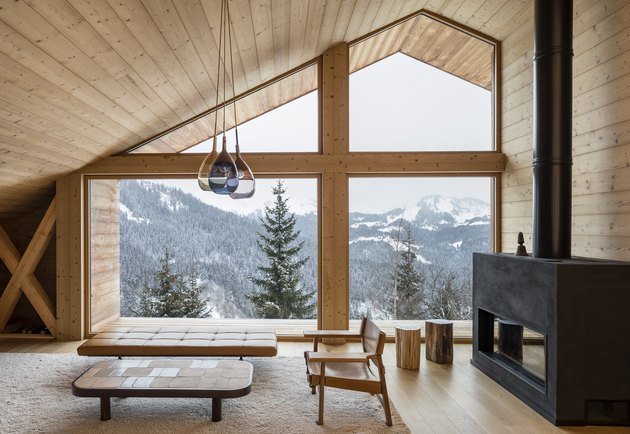 pine-covered chalet living room with wood burning stove and minimal decor