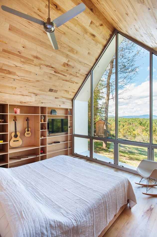 small room in cabin with builtin bookcase and forest mountain views large windows