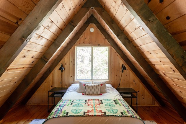 mountain A-frame cabin loft bedroom with matte black nightstands and wall sconces