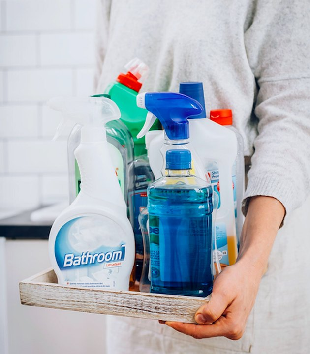 woman holding household cleaners