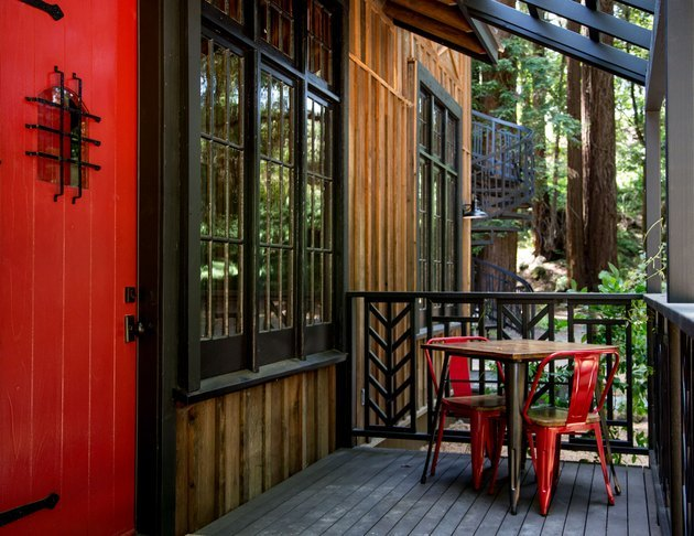 restored cabin facade with red door and small bistro table and chair set