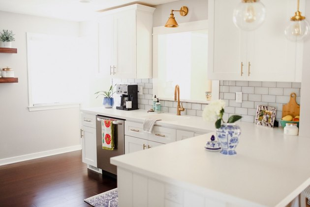 White and brass modern kitchen with solid surface countertops