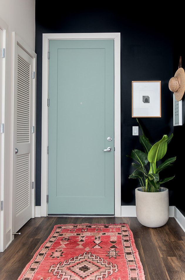 minimalist entryway design with colorful door and dark walls and rug