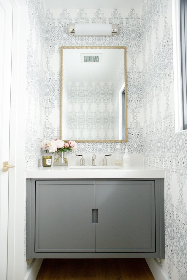elegant bathroom lighting idea in gray powder room with batik wallpaper