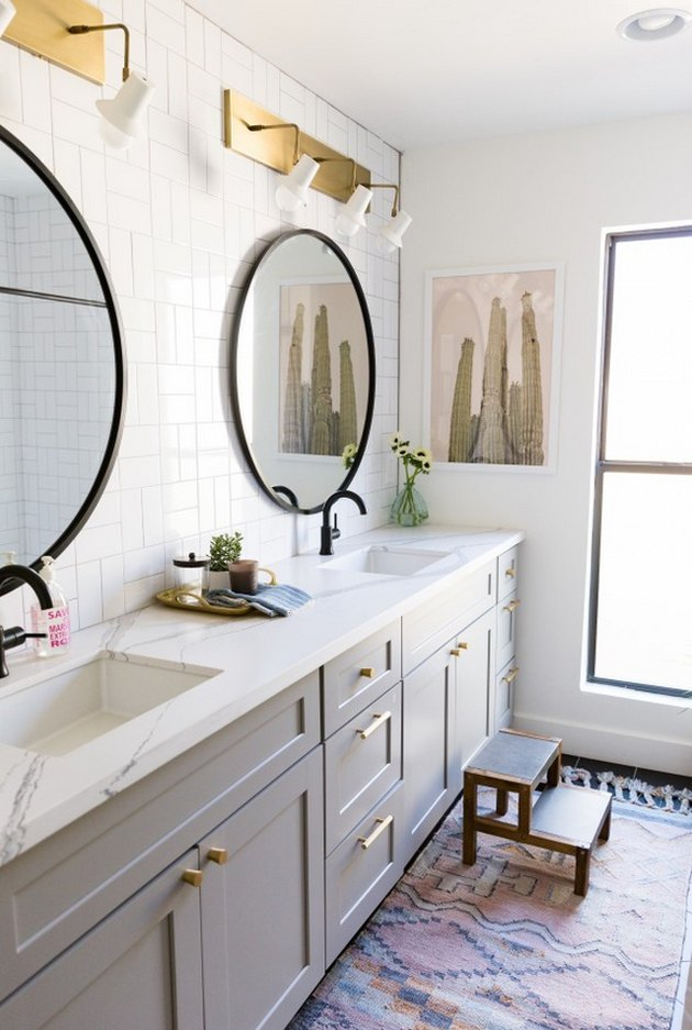 double sink bathroom lighting idea with trio of brass wall sconces above each mirror