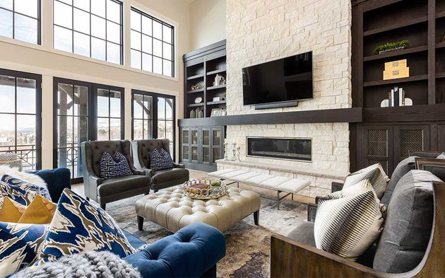 transitional family room with two leather high back chairs, leather tufted ottoman, blue tufted couch, stone mantel