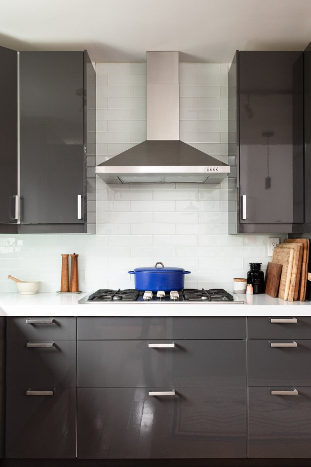 grey kitchen cabinets, stove top and stainless steel range hood