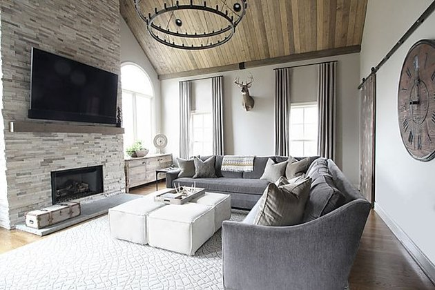 transitional family room with gray sectional couch, white ottomans, wood ceiling, iron chandelier.