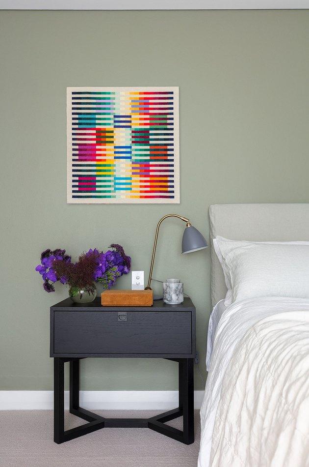 sage minimalist bedroom idea with bold artwork