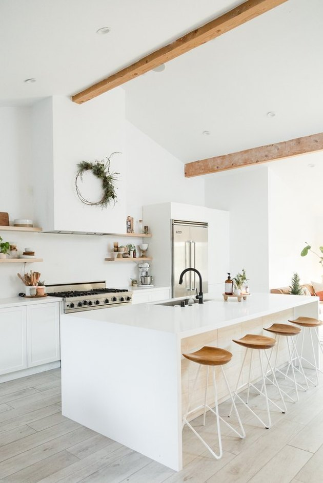 white kitchens with wood floors, exposed wood beams, and wood bar stools