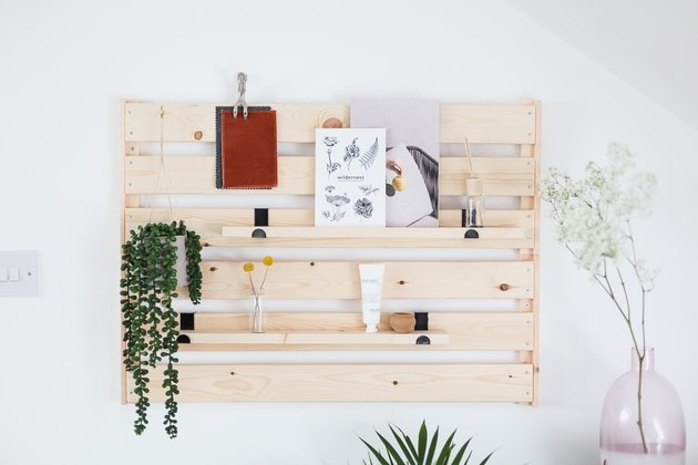 Wood wall shelving and organization unit, with a plant and artwork.