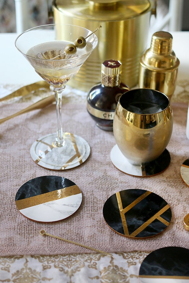 Art deco DIY project with black, gold, and marble coasters among cocktail hour items