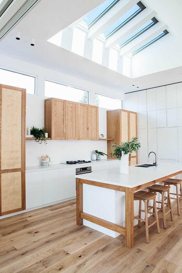 white kitchens with wood floors, vaulted ceiling with skylights, and wood cabinets
