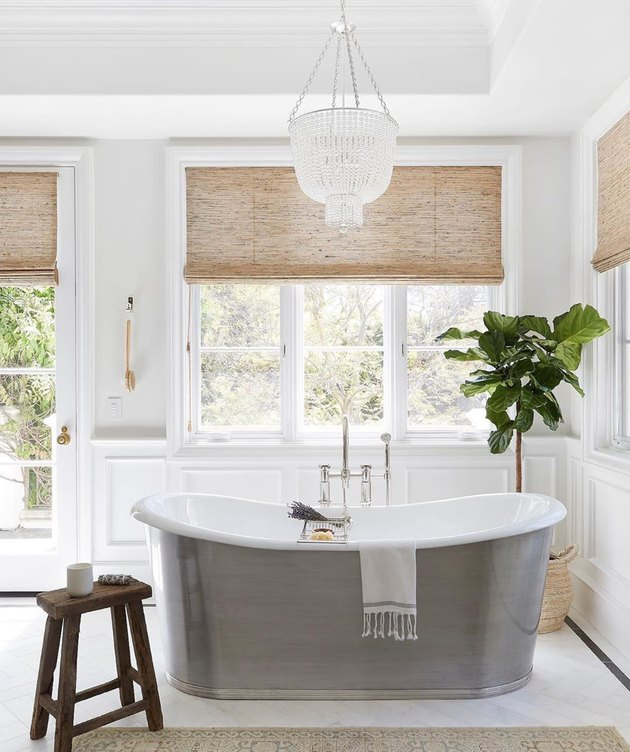 elegant bathroom lighting idea with silver tub and crystal chandelier
