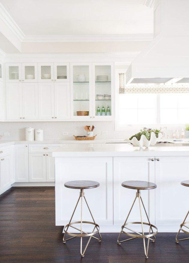 white kitchens with wood floors, white cabinets, and white range hood