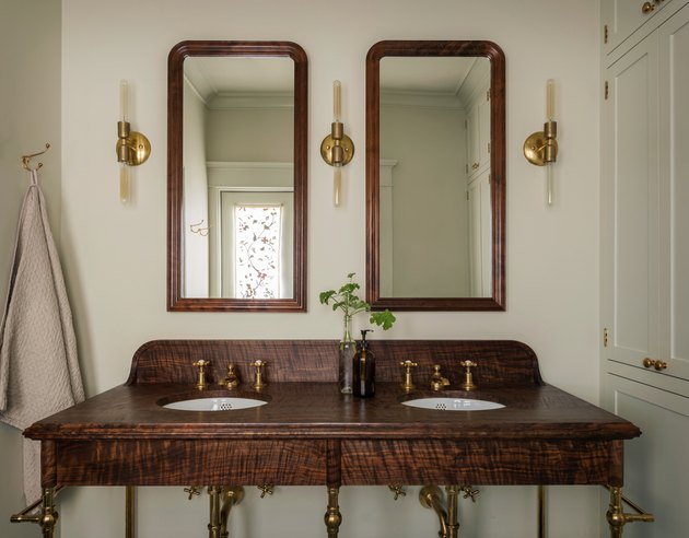 elegant bathroom lighting idea with wood vanity, builtins and slim sconces