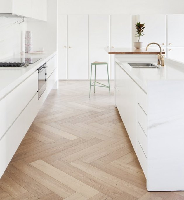 white kitchens with wood floors in herringbone pattern and brass faucet
