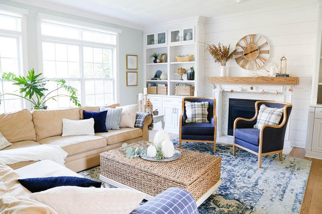 blue and white coastal family room with wicker coffee table ottoman