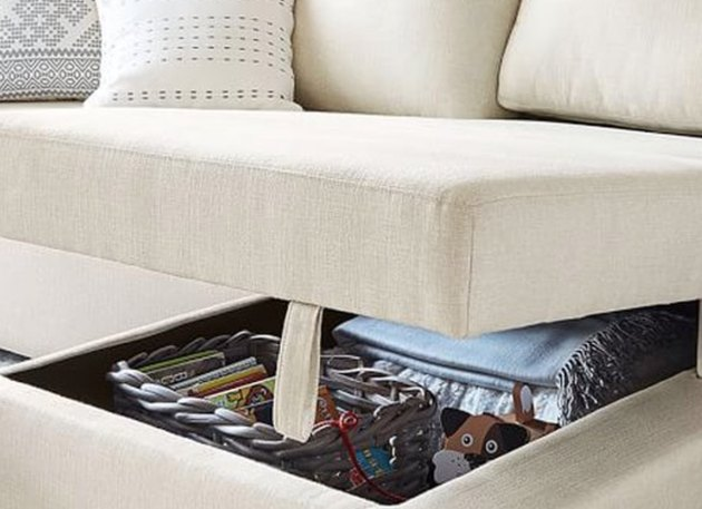 family room storage in cream sectional couch with under seat storage and throw cushion.