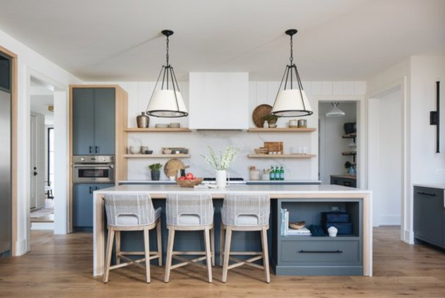 Waterfall kitchen island with gray base and two farmhouse pendant lights