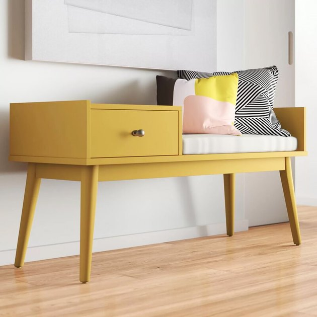 family room storage with yellow bench with drawer, throw pillows, white cushion and wood floors.