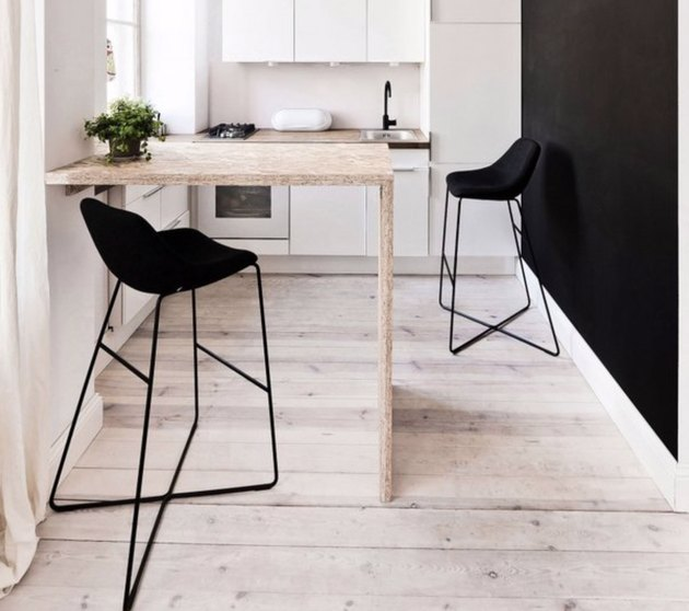 Small waterfall kitchen island in white kitchen with light wood floors, black accent wall and black barstools