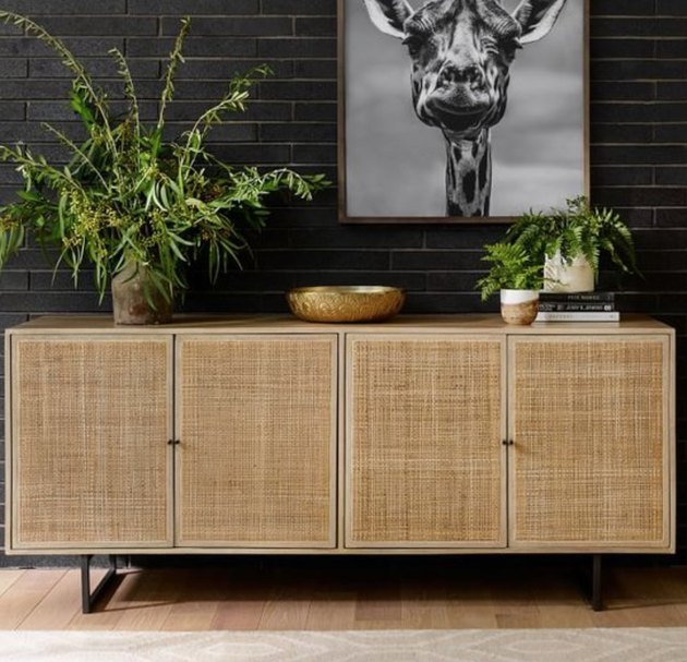 family room storage with beige cane credenza and plants