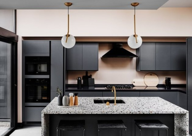 Kitchen with black cabinets and counters, terrazzo waterfall kitchen island, sink.
