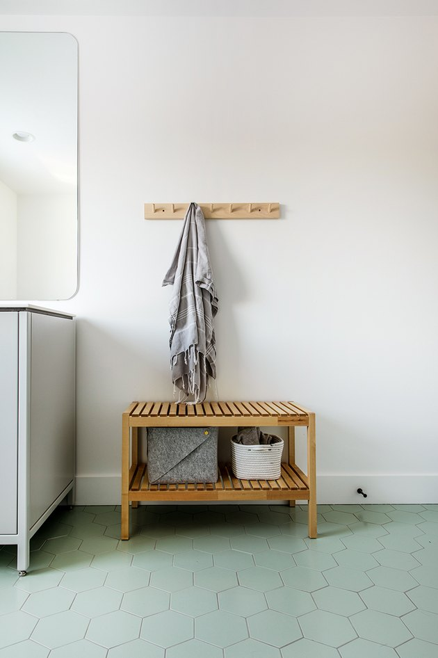 teak wood bench with minimalist bathroom storage and green hex tile