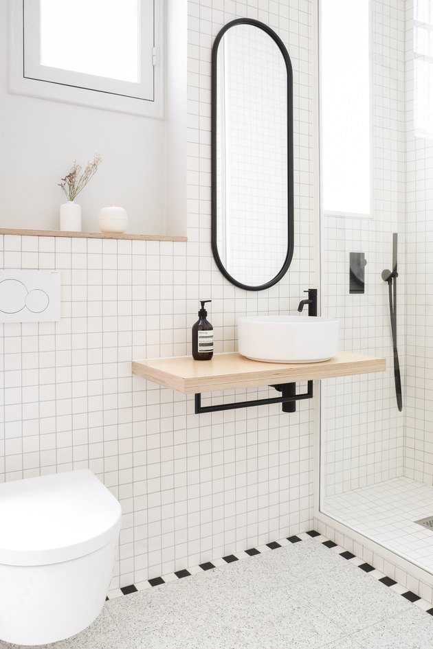 black and white minimal bathroom with floating sink and storage