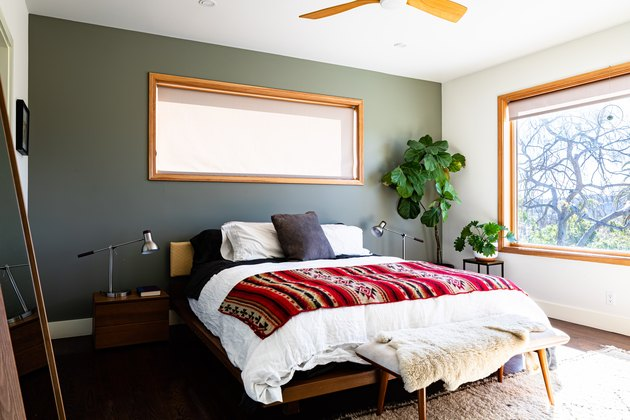 Bedroom with green wall, colorful red blanket on white duvet cover