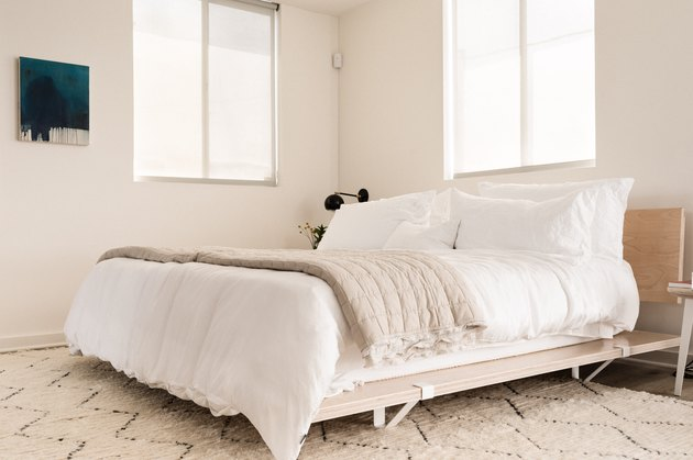 Wood bed frame with white bedspread in California modern bedroom