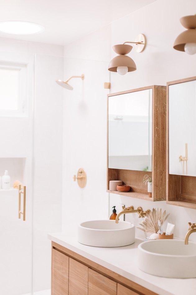 white bathroom with glass shower door and minimalist bathroom storage
