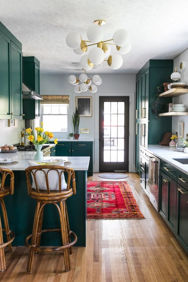 Green boho room with green cabinets and midcentury-inspired lighting