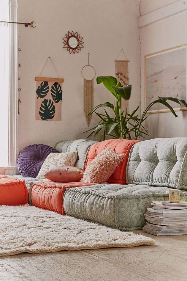 Boho living room full of colorful floor cushions and furry carpet