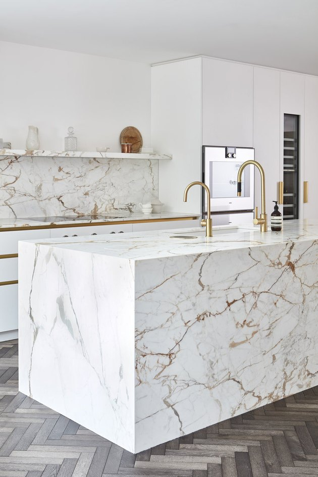 wraparound marble kitchen island with gold veining and brass faucets