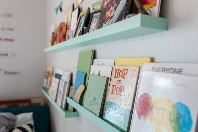 Baby blue bookshelves in kid's room on white wall