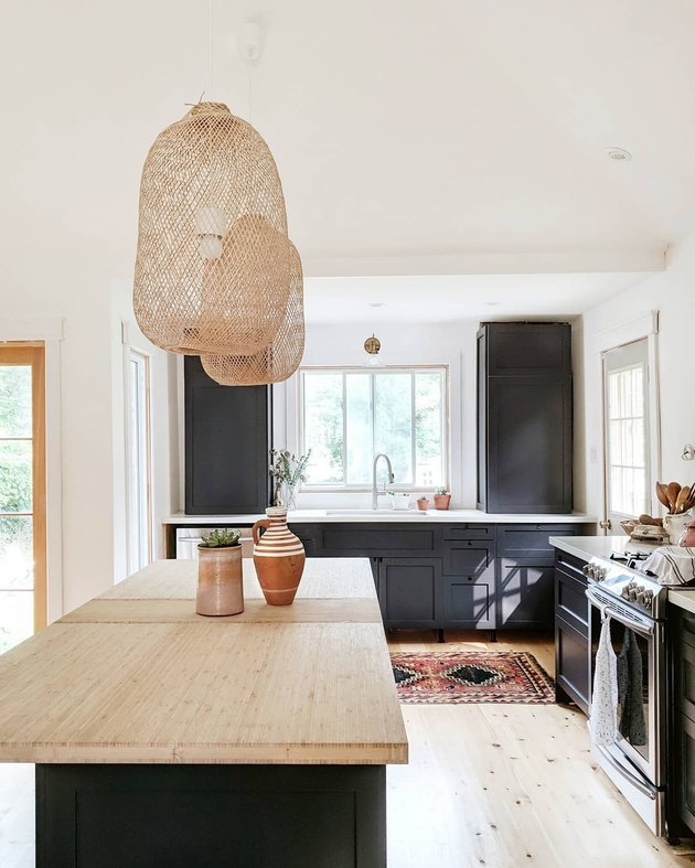 masculine boho decor in white kitchen with black cabinets and cane pendants