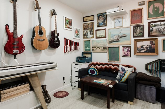 Music room and gallery with musical instruments and artwork on the walls and floor.