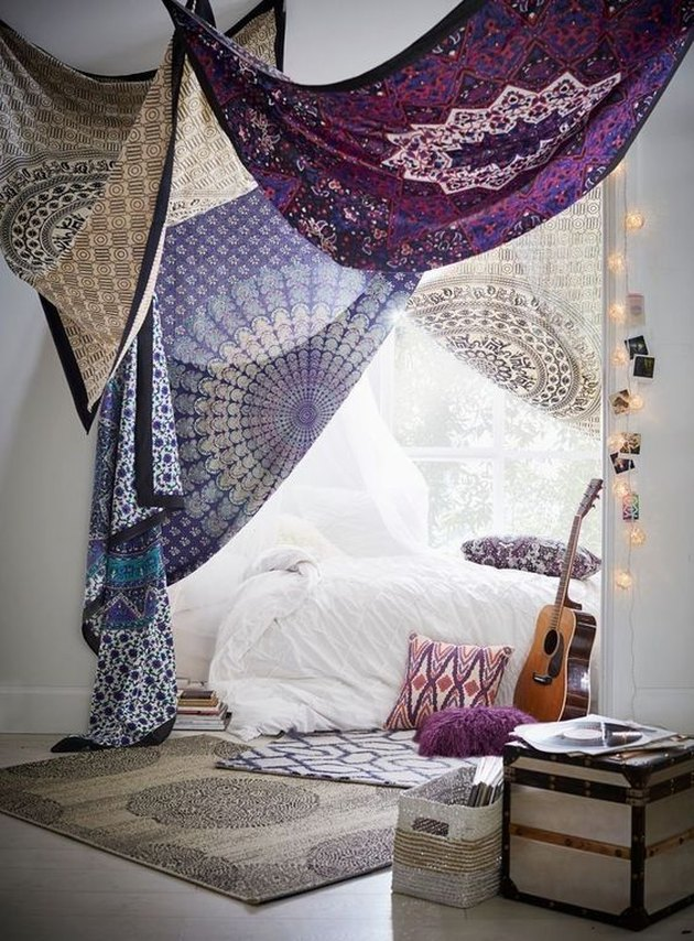 Boho bedroom with draped tapestries by white bed