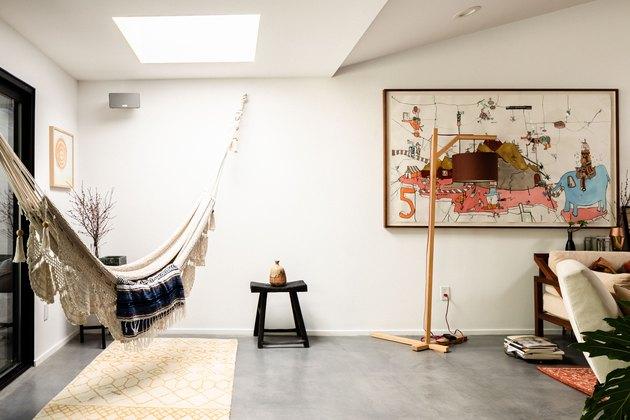 Hammock below skylight in artsy apartment with cement floors.