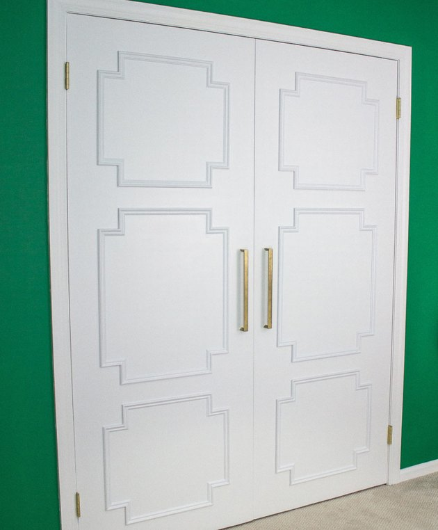 Art deco DIY project with white closet doors featuring molding and bright green wall