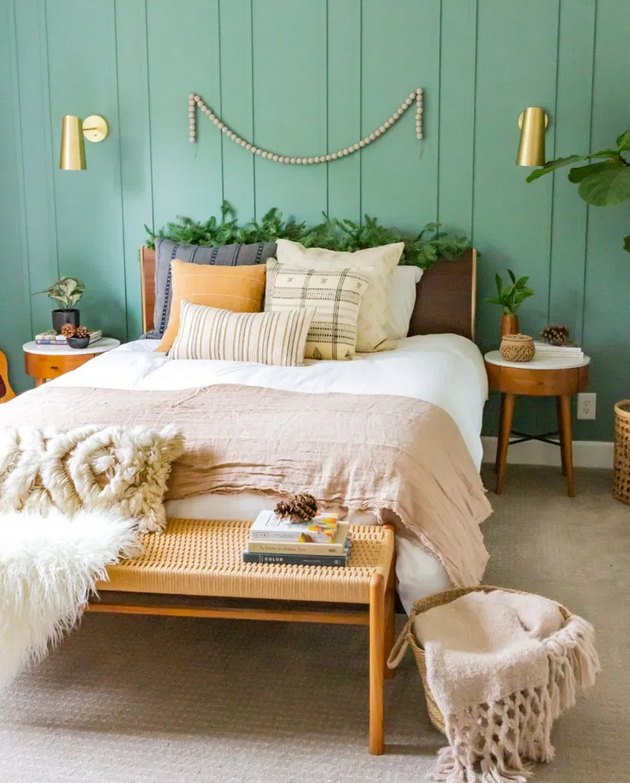 Green boho room with green board and batten accent wall and neutral bed linens
