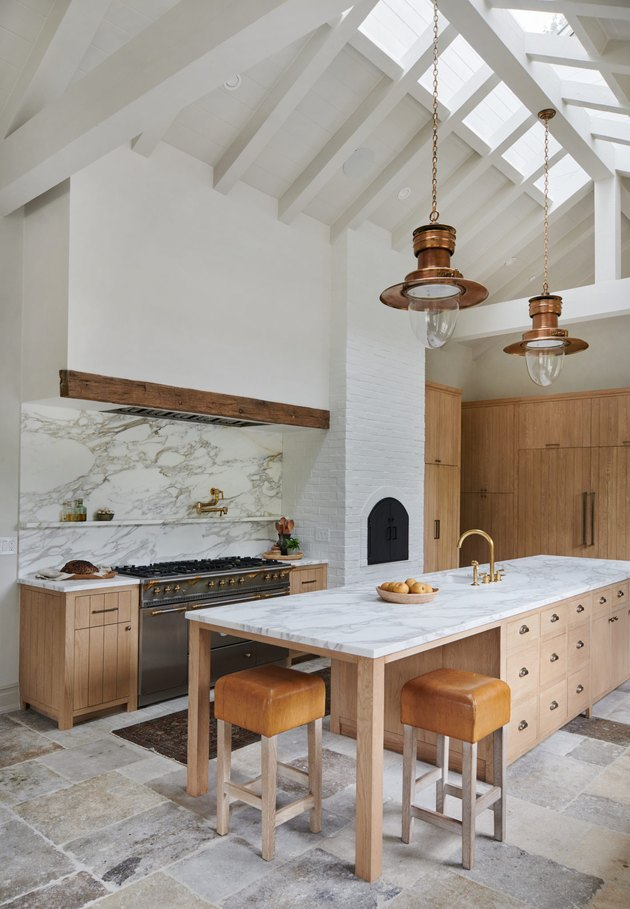 rustic white kitchen with high ceilings and marble kitchen island