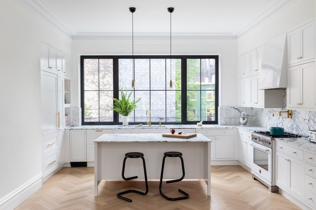 Paonazzo marble kitchen island in kitchen with wood floors and black counter stoold